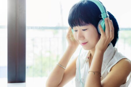 Asian woman wearing headphones and listening music with blurred background for entertainment, relaxation and stay at home concept Imagens