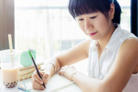 Asian woman writing on a notebook with a plastic cup of bubble tea against blurred