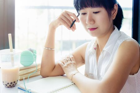 Asian woman holding a pen and thinking about work with a plastic cup of bubble tea against blurred Imagens