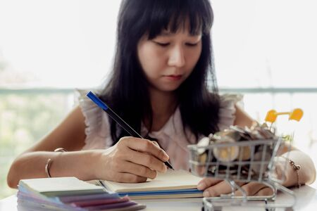 Selective focus of Asian woman's hand writing on a notebook with blurred money and coins in a shopping cart for business and financial planning concept