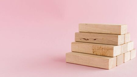 Wooden toy staircase on pink background for step to goal success concept