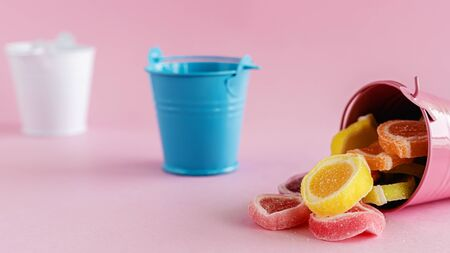 Colourful fruit Jelly candy in a pink bucket against pink background for food and snack concept