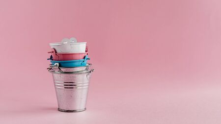 Mini colored tin pails or buckets on pink background with copy space