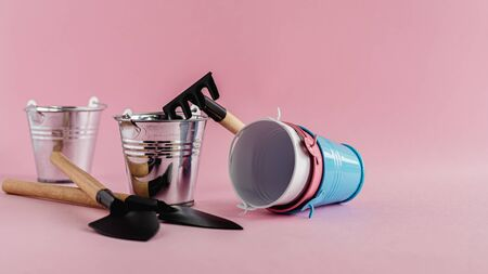 Gardening tools with tin pails or buckets on pink background for planting concept Imagens
