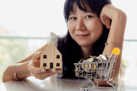 Selective focus of asian woman's hand holding a wooden house model with full of coins in shopping cart for planning, savings and property investment concept