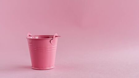 Mini colored tin pail or bucket on pink background with copy space for household items concept Imagens