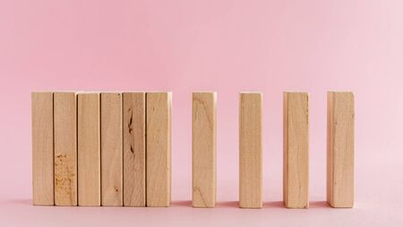 Wooden toys arranged in a horizontal row on pink background for leisure activities concept Imagens