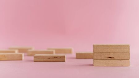 Wooden toys arranged on pink background for leisure activities concept