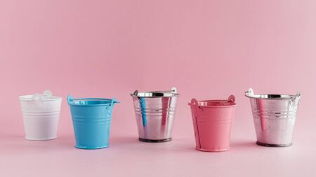 Mini colored tin pails or buckets on pink Imagens