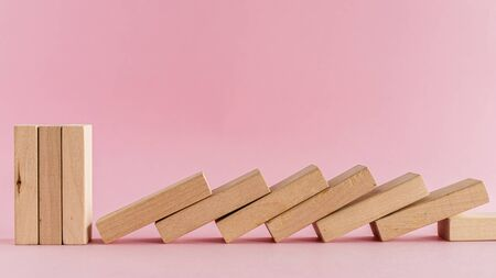The wooden toys arranged in a horizontal row but the next others falling down on pink background for leisure activities concept Imagens - 147429593