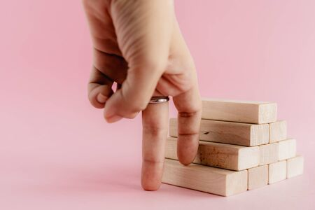 Fingers moving step up the wooden toy staircase on pink background for step to goal success concept