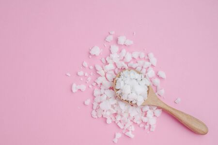 Sea salt in a wooden spoon on pink background for seasoning or preserving food