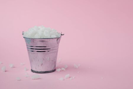 Sea salt in a tin bucket on pink background for seasoning or preserving food