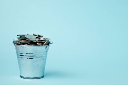 Full of money coins in a tin bucket on blue background for investment, business, finance and saving money concept
