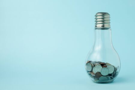 Coins in light bulb bottle shape on blue background with copy space for investment, business, finance and saving money concept