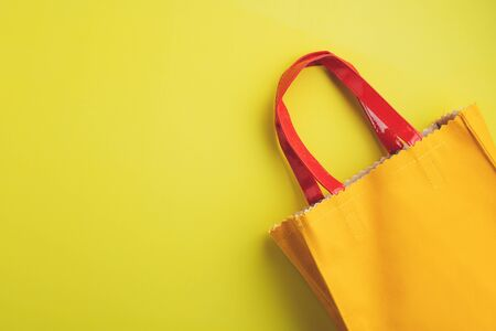Yellow leather reusable bag on yellow background with copy space for green environmentally friendly concept