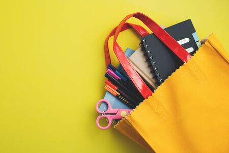 Learning supplies with notebook, coloured pen and scissors in yellow bag on yellow background with copy space for education and back to school concept