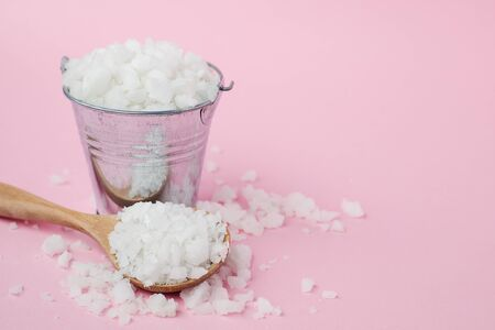 Sea salt in a wooden spoon and a tin bucket on pink background for seasoning or preserving food