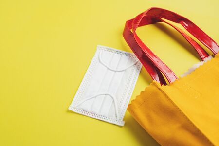 Hygiene face mask with shopping bag on yellow background for healthcare and new normal or new way of living concept