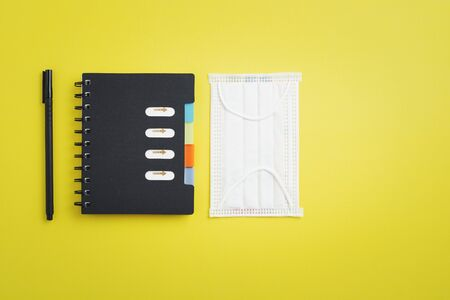 Hygiene face mask with office supply as notebook and a pen for new normal or new way of living concept