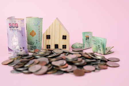 Wooden house model with Thai currency banknote and money coins on pink background for business, finance and property investment concept