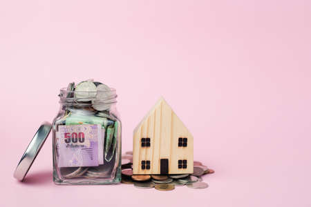 Wooden house model with Thai currency banknote and money coins in the glass jar on pink background for business, finance and property investment concept