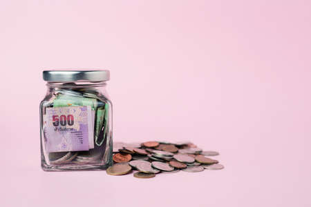 Thai currency banknote and coins in the glass jar on pink background for business, finance, investment and saving money concept Imagens