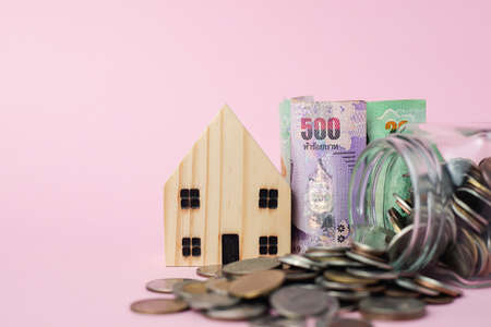 Wooden house model with Thai currency banknote and money coins in the glass jar on pink background for business, finance and property investment concept Imagens - 150884824