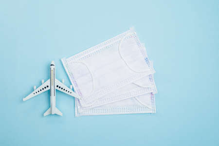 White airplane model with hygiene face mask on blue background for travelling and healthcares concept Imagens