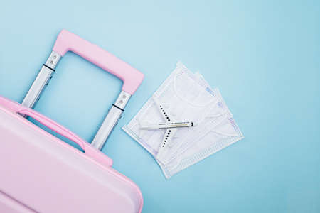 Pink luggage with white airplane model and hygiene face mask on blue background for travelling and new normal or new way of living concept