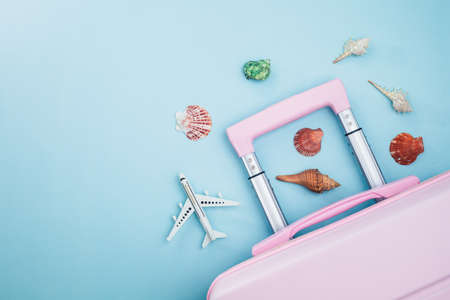 Pink luggage with white airplane model and sea shells on blue background for travelling and summer beach concept Imagens