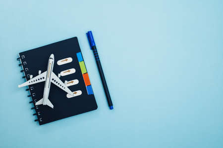 White airplane model with a checklist diary on blue background for travel planning concept