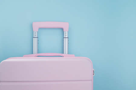 Pink luggage on blue pastel colored background for traveling concept Imagens