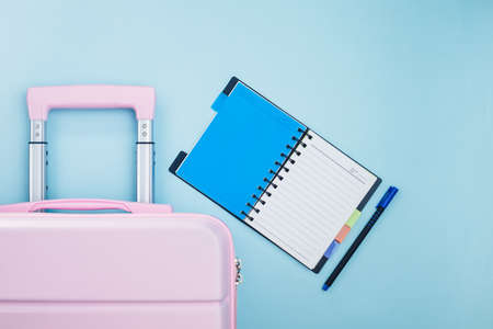 Pink luggage with a checklist diary on blue background for travel planning concept Imagens