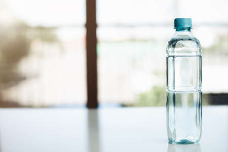 Water bottle on the table against blurred background for drinking and beverages concept