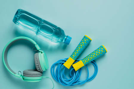 Fresh drinking water, jump rope and headphones on blue background for sports and healthcare concept