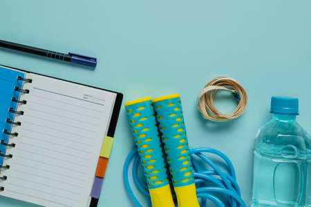 Notebooks with measure tape, fresh drinking water, jump rope on blue background for healthy diet taking notes concept