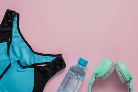 Sport bra for exercise, fresh drinking water and headphones on pink background for sports and healthcare concept Imagens