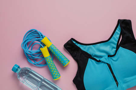 Sport bra for exercise, fresh drinking water and jump rope on pink background for sports and healthcare concept Imagens