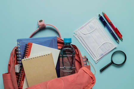 Learning supplies with hygiene face mask in a pink student backpack on blue background for education and back to school in an outbreak of plague situation concept Imagens