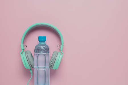 Fresh drinking water with headphones on pink background for healthcare and relaxation concept Imagens