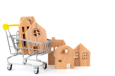 Wooden house model in the shopping cart on white background for housing and property concept