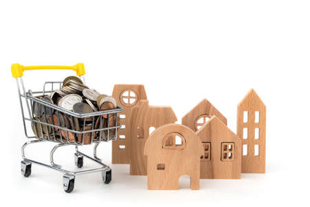 Wooden house model with full of coins in shopping cart on white background for business, finance and property investment concept