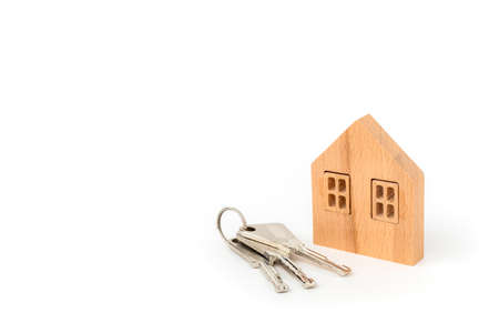 Wooden house model with keys on white background for housing and property concept Imagens