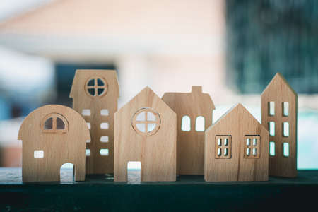 Wooden house model against blurred outdoor background for housing and property concept Imagens