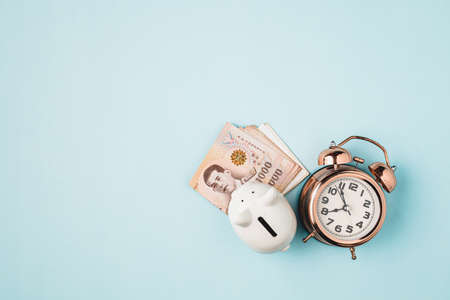 Saving piggy bank with Thai currency, 1000 Baht, money banknote of Thailand and bell alarm clock on blue background for business, finance and time management concept