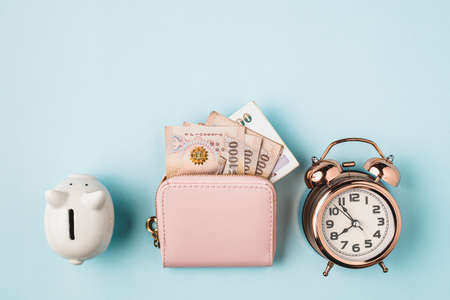 Saving piggy bank with wallet of Thai currency, 1000 Baht, money banknote of Thailand and bell alarm clock on blue background for business, finance and time management concept Imagens