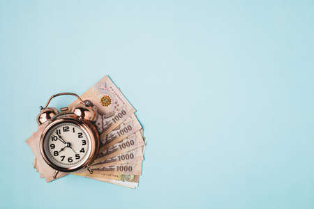Bell alarm clock  with Thai currency, 1000 Baht, money banknote of Thailand on blue background for business, finance and time management concept