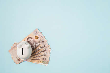 Saving piggy bank with Thai currency, 1000 Baht, money banknote of Thailand on blue background for business and finance concept Imagens