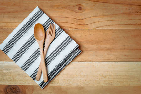 Spoon and fork with napery on wooden table for utensil and kitchenware concept